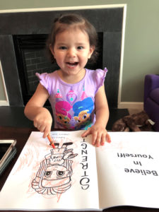 Child coloring a coloring book